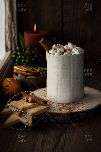 Aromatic cacao with marshmallow and cinnamon stick served on wooden table with cookies in star shape prepared for Christmas celebration