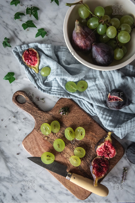 Top view of delicious grapes and figs arranged on marble table with cutting board and kitchen towel