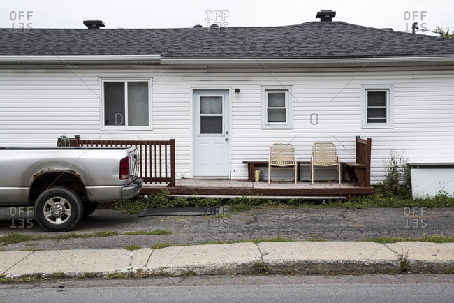 A pickup truck and two chairs outside a house in Longueuil, Canada