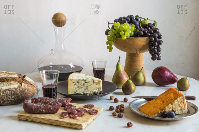 Cheese, meat, bread and fruit on a table with wine