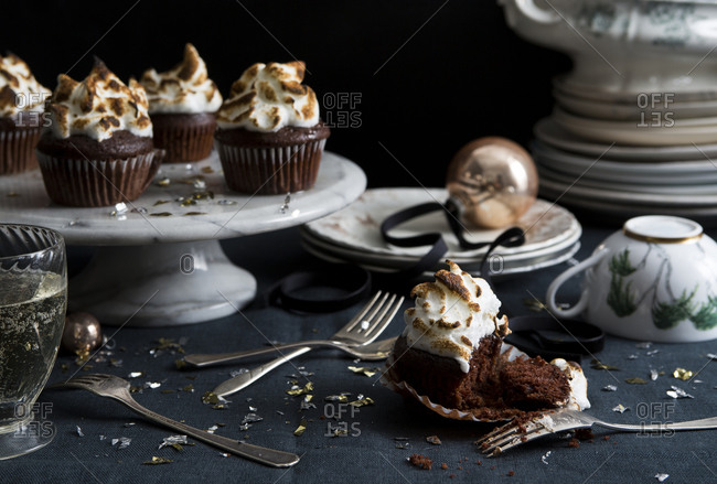 Chocolate cupcakes with marshmallow meringue on a party table with confetti