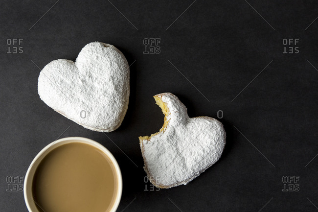 Overhead view of coffee beside heart donuts partially eaten