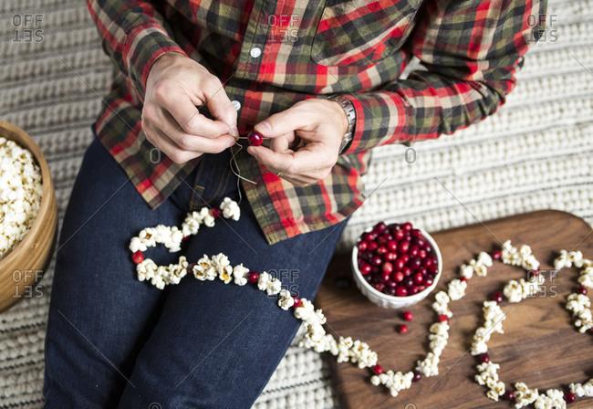 Man stringing popcorn and cranberries into garland