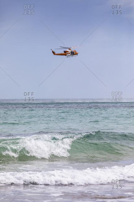 Rescue helicopter training over sunny ocean, Adelaide, Australia