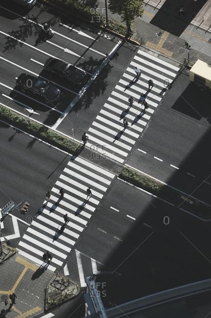Aerial view pedestrians crossing city street at crosswalk, Tokyo, Japan