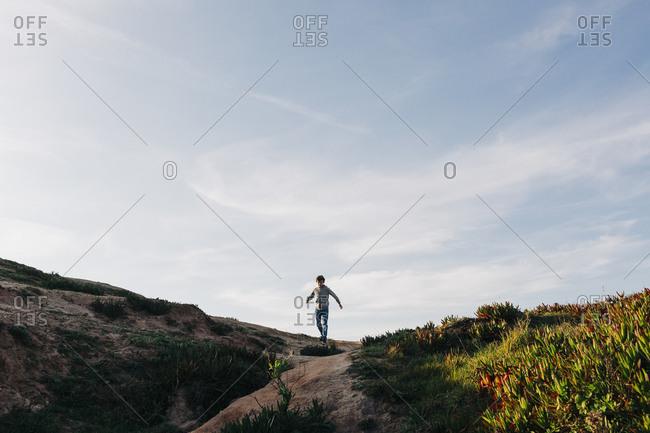 Boy running on beach hill, Peniche, Portugal