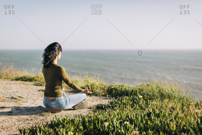 Serene woman meditating on sunny cliff overlooking sea