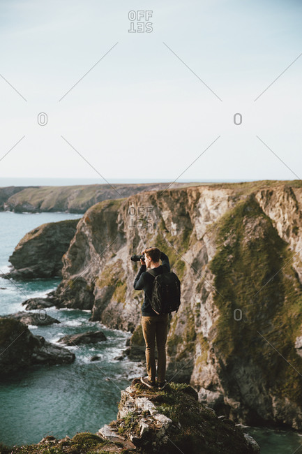 Male photographer on scenic ocean cliff, Bedruthan Steps, Cornwall, UK