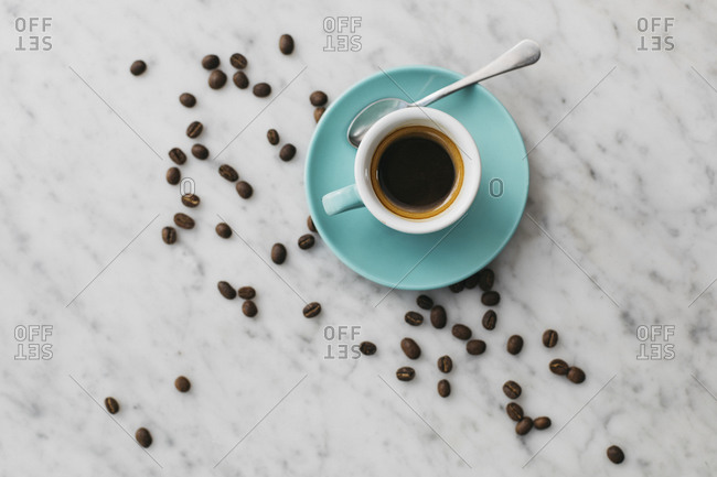 Coffee beans scattered around espresso cup