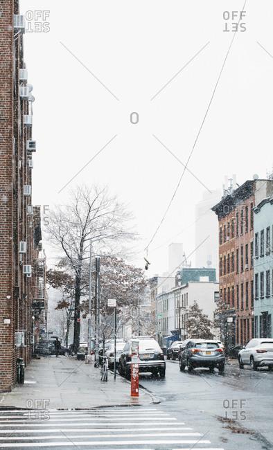 Snow falling over urban street, Brooklyn, New York, USA