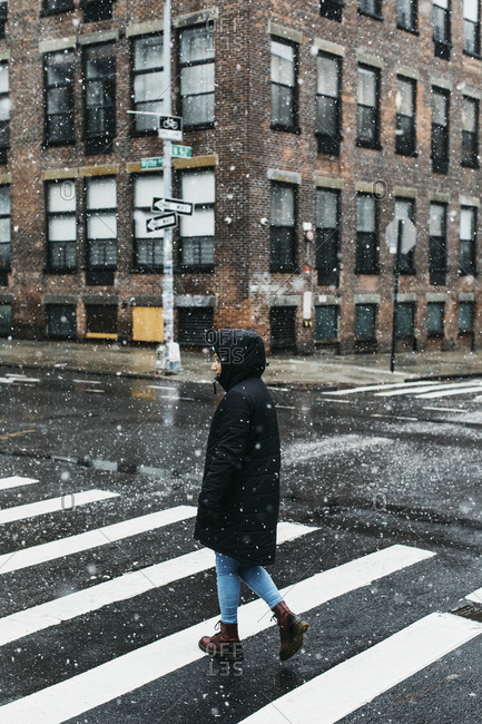 Young woman in warm jacket crossing snowy urban street, New York City, New York, USA