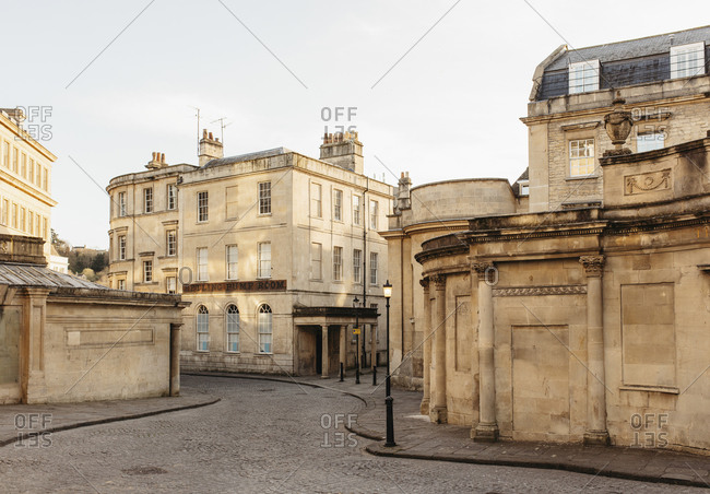 Buildings along empty winding road, Bath, Somerset, UK