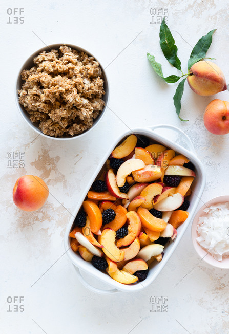 Raw peaches, apricots and blackberry crumble dessert in a baking tray ready for the oven