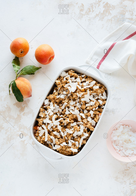 Top view of a fruit crumble dessert in a baking tray ready for the oven