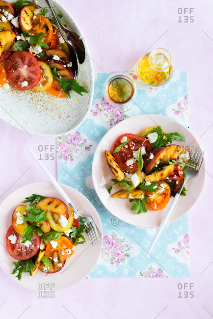 Grilled peaches and tomato salad with feta cheese and green mix being served on two plates