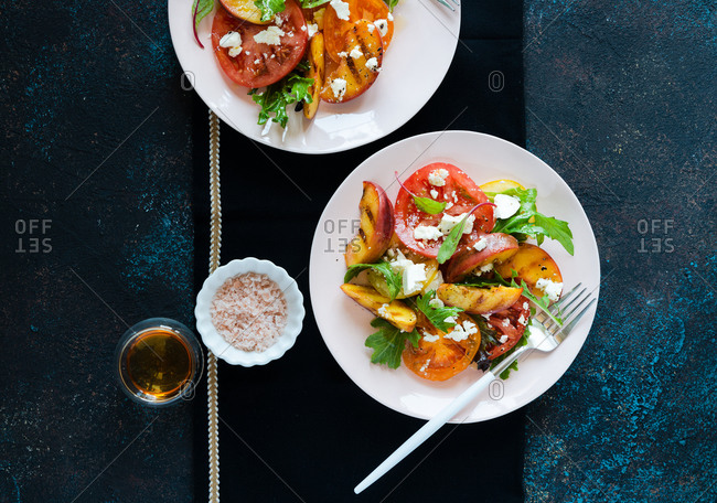 Overhead view of grilled peaches and tomato salad with feta cheese and green mix on two plates