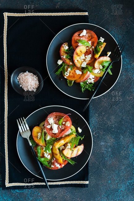 Grilled peaches and tomato salad with feta cheese and green mix served on two black plates