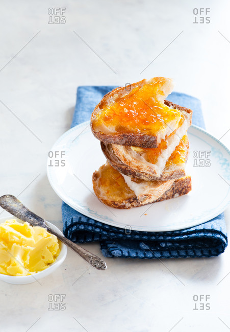 Breakfast toast with butter and orange jam on white plate over light background