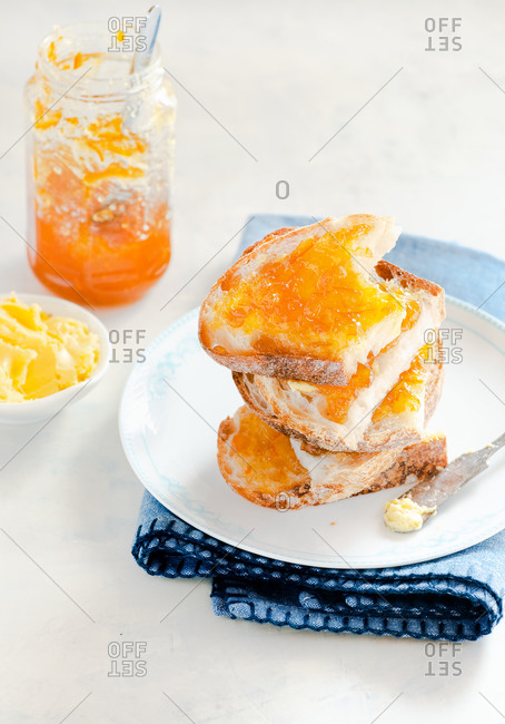 Toast with butter and orange jam on white plate over light background