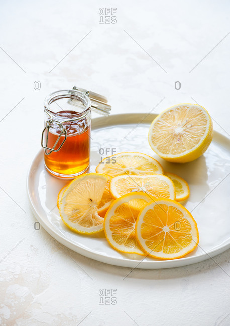 Lemon slices on plate with honey on the side