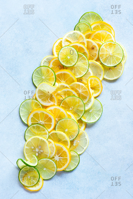 Lemon and lime slices on light blue background top view