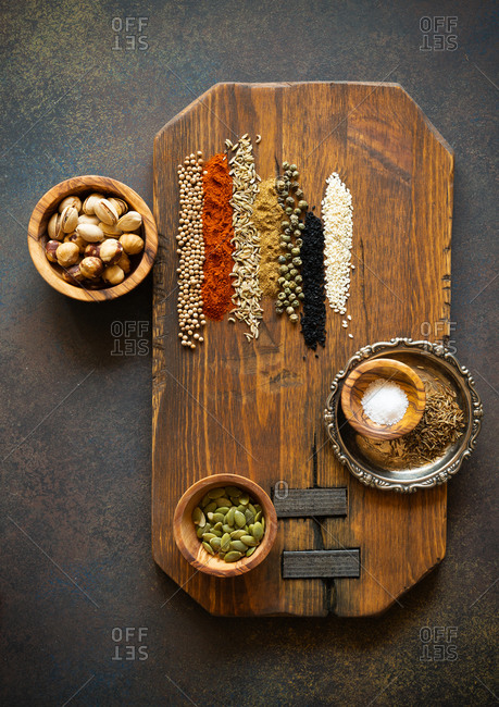 Spices and nuts for dukkah on a wooden board viewed from above