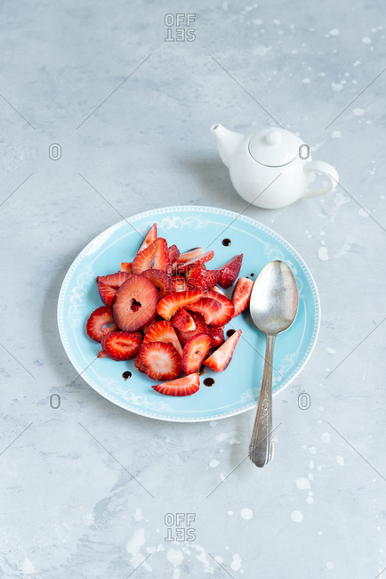 Top view of strawberry slices with balsamic vinegar on a plate