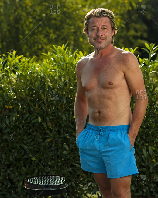 Portrait of a shirtless man standing with hands in his blue short pockets