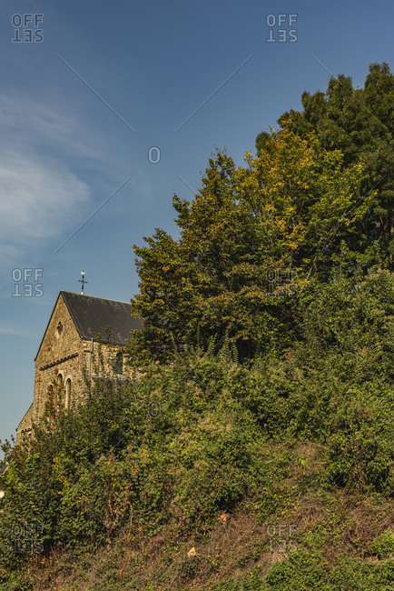 Old stone church on hilltop by trees