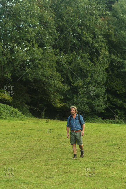 Man backpacking through a green field