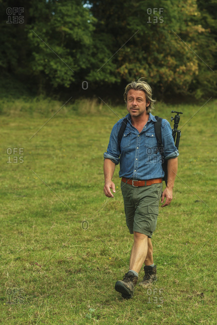 Male photographer backpacking through a green field