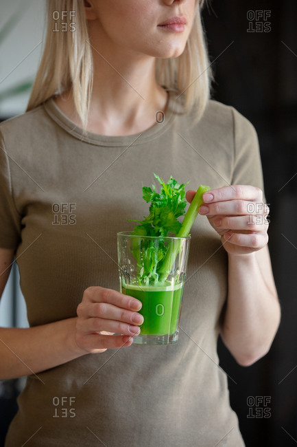 Blonde woman holding a glass of green juice with a celery stalk at home