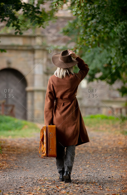 Woman in vintage coat and hat with suitcase in autumn alley near a castle