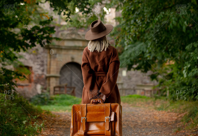 Rear view of woman in vintage coat and hat with suitcase in autumn alley near a castle