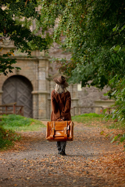 Woman in vintage coat and hat with suitcase walking toward castle
