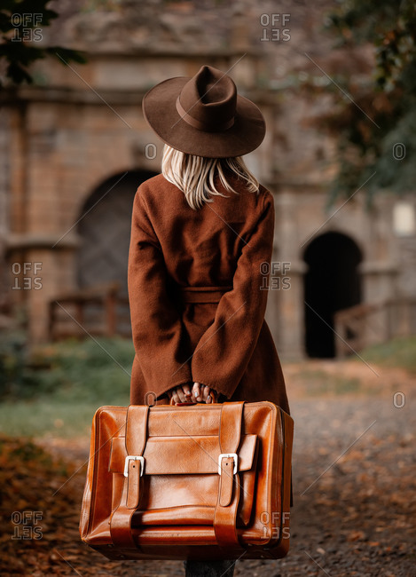 Back view of woman in vintage coat and hat with suitcase in autumn alley near a castle