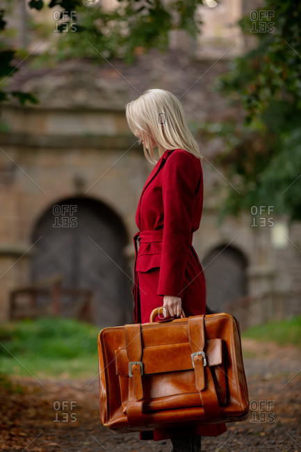 Blonde woman in red coat with suitcase on alley near the castle in autumn season