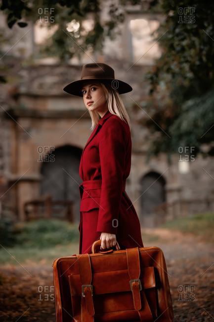 Beautiful woman in red coat with suitcase on alley near the castle in autumn season