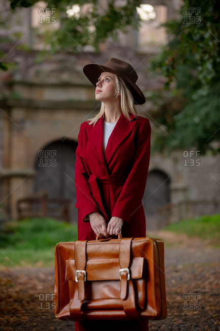 Woman in vintage red coat and hat with suitcase in autumn alley near the castle