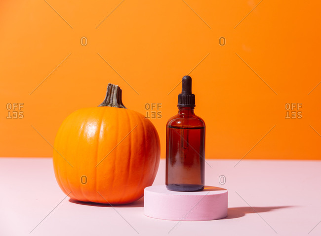 Cosmetic oil and pumpkin on orange background