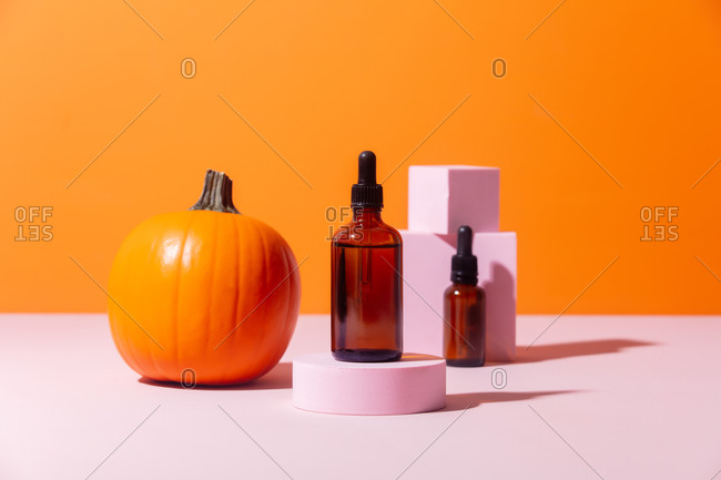 Cosmetic oil in glass bottles and pumpkin on orange background
