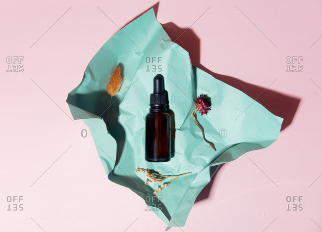 Cosmetic oil bottle with crumpled paper on light surface