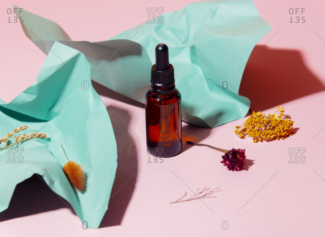 Cosmetic oil bottle with crumpled paper and herbs on light surface