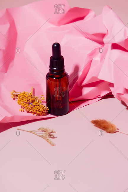 Cosmetic oil bottle with crumpled pink paper and herbs on light surface