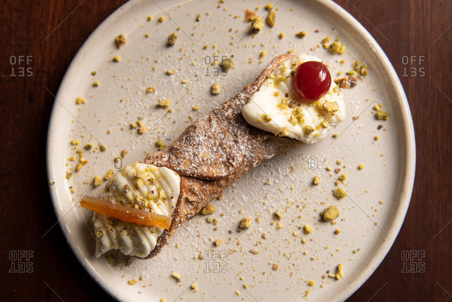 Cannoli on a plate garnished with cherry and pistachios