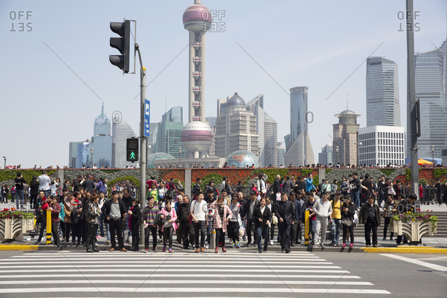 Shanghai, China - April 3, 2016: Pedestrians crossing at a crosswalk on Nanjing Street with Pudong business district in background
