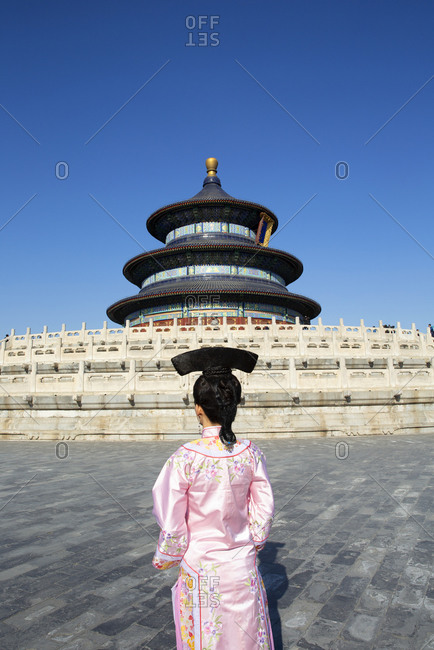 Rear view of a young lady in period costume in front of the Temple of Heaven at the Forbidden City Palace, Beijing, China