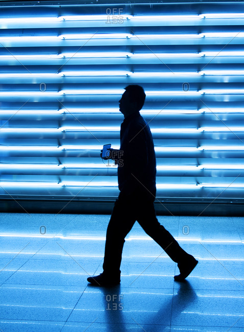 Shanghai, China - March 25, 2016: Chinese man walking by a wall of light at Shanghai international airport. holding a smart phone