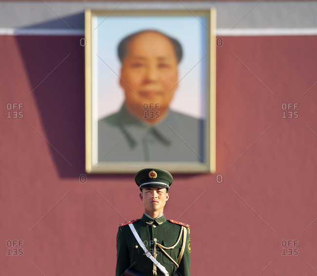 Beijing, China - March 22, 2016: Guard out in front of portrait of Mao Tse Tung hanging on entrance to The Forbidden City palace complex