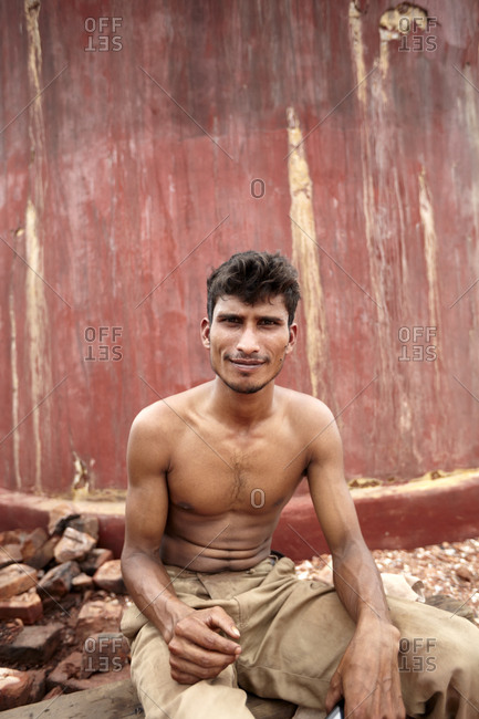 Chittagong, Bangladesh - May 12, 2013: Portrait of a young man taking break while working in a brick factory